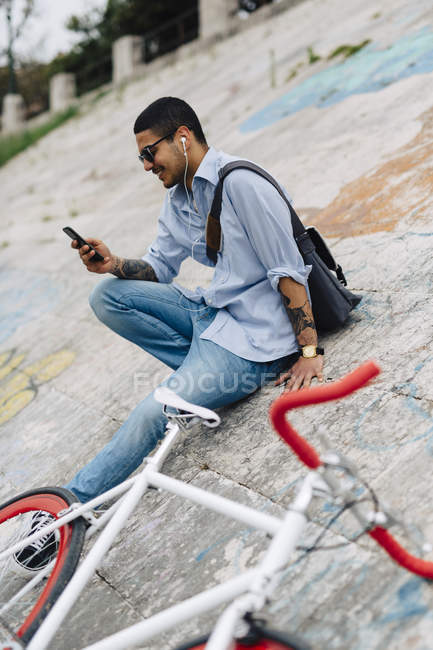 Young man with a bicycle sitting on a wall looking at cell phone — Stock Photo