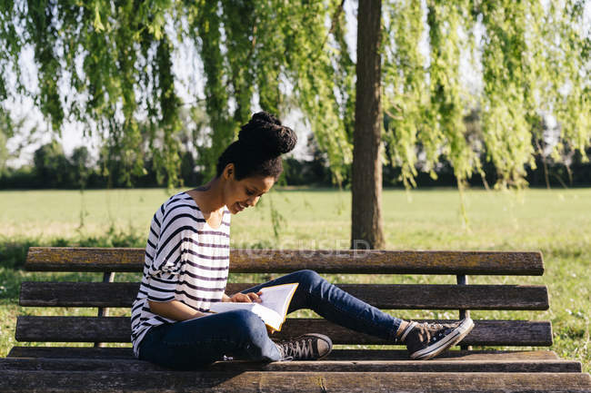 Young woman sitting on park bench reading a book — Stock Photo