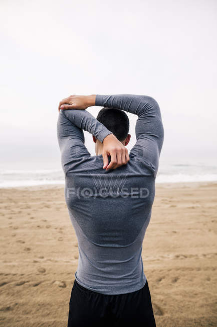 Sportive young man stretching on beach — Stock Photo