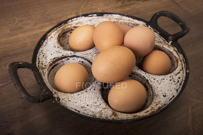 Ovos castanhos frescos na panela velha na mesa de madeira — Fotografia de Stock