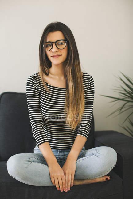Mujer joven sentada con las piernas cruzadas en el sofá y mirando a la cámara - foto de stock