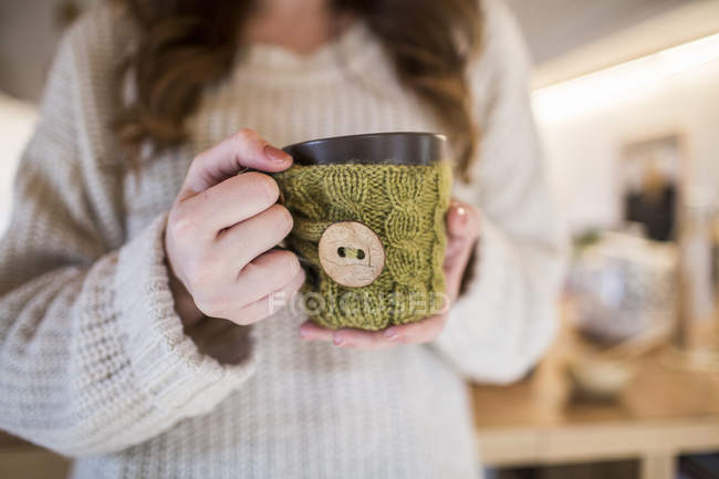 Young woman at home holding cup of coffee — Stock Photo