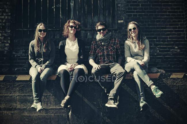 Quatro amigos com óculos de sol sentados em frente ao prédio industrial à luz do sol — Fotografia de Stock