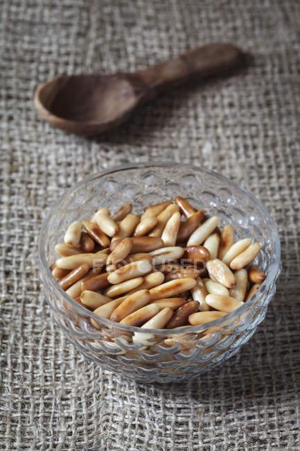 Чаша підсмаженими кедровими горішками на оперезана з дерев'яною ложкою — стокове фото