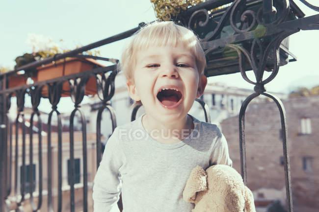Blonder Junge steht mit offenem Mund auf Balkon — Stockfoto