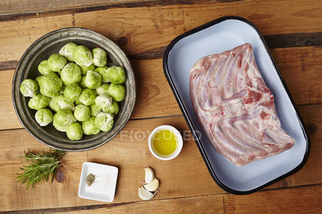 Sucklng pig roasted with brussels sprouts over wooden surface — Stock Photo