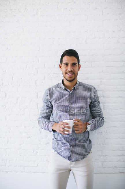 Jovem empresário de pé com xícara de café contra a parede e olhando para a câmera — Fotografia de Stock