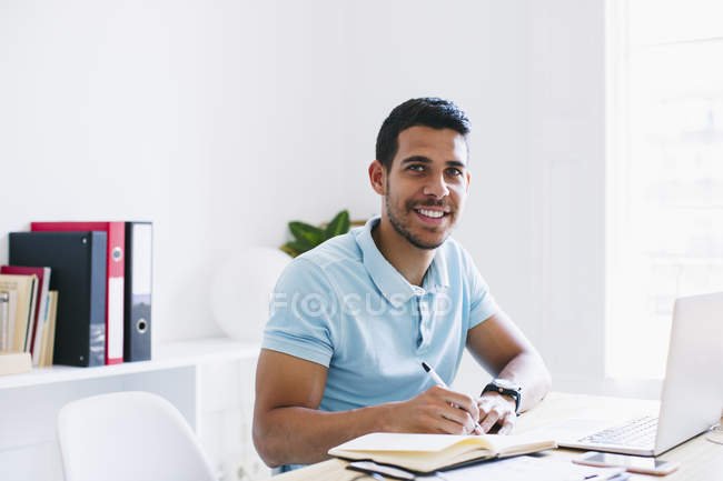 Young man writing in notebook in office and smiling at camera — Stock Photo