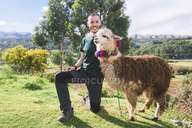Peru, Cusco, portrait of happy tourist posing with llama — Stock Photo