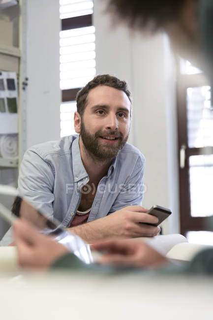 Creative professional at desk looking at colleague — Stock Photo