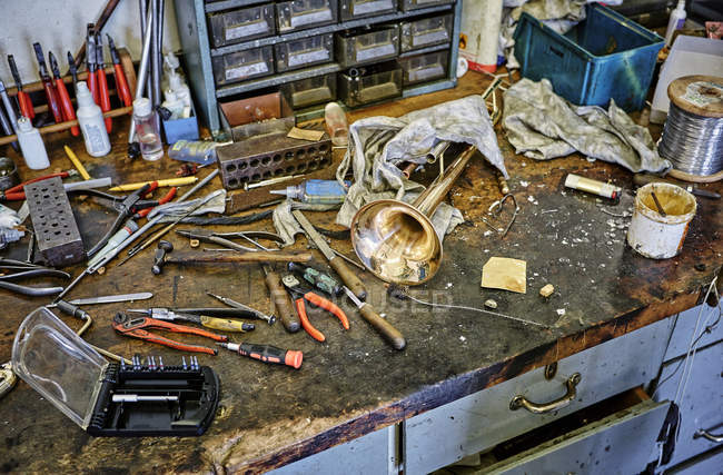 Elevated view of old workbench with tools and trumpet — Stock Photo