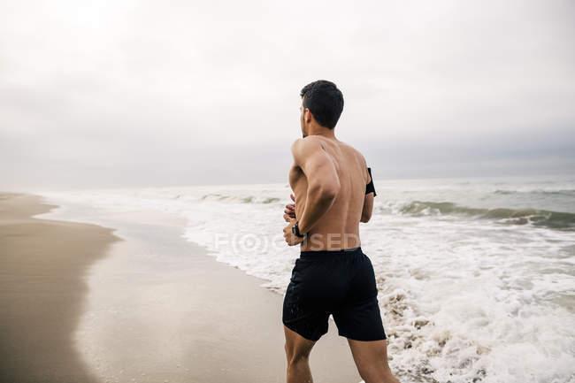 Hombre joven en playa - foto de stock