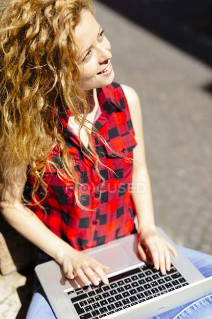 Mujer sonriente al aire libre usando computadora portátil - foto de stock