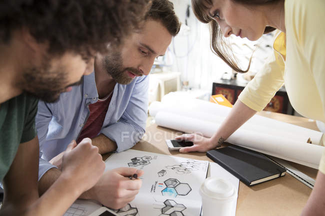 Three colleagues discussing draft in office — Stock Photo
