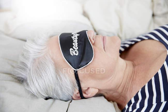 Femme avec masque de sommeil couché sur le lit — Photo de stock