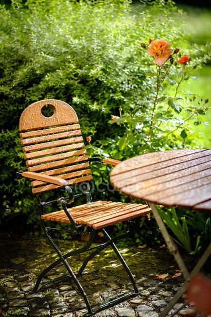 Garden table and chair, summer rain — Stock Photo