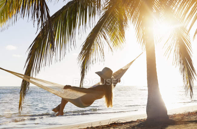 Dominican Rebublic, Young woman in hammock looking out over tropical beach — Stock Photo