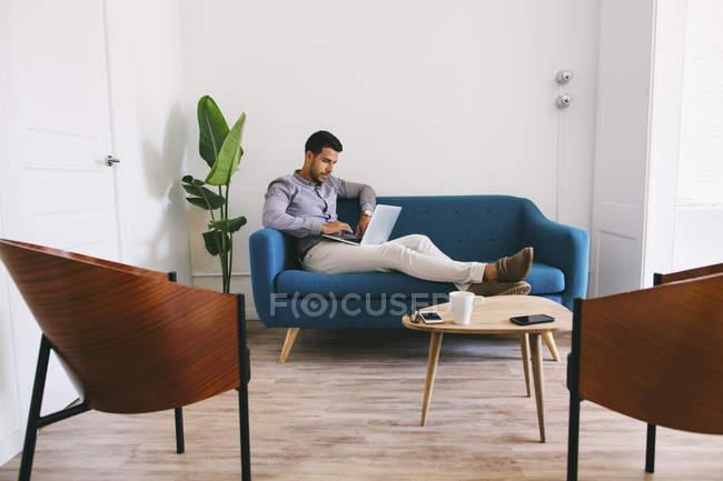 Бизнесмен сидит на диване в офисе с помощью ноутбука — стоковое фото