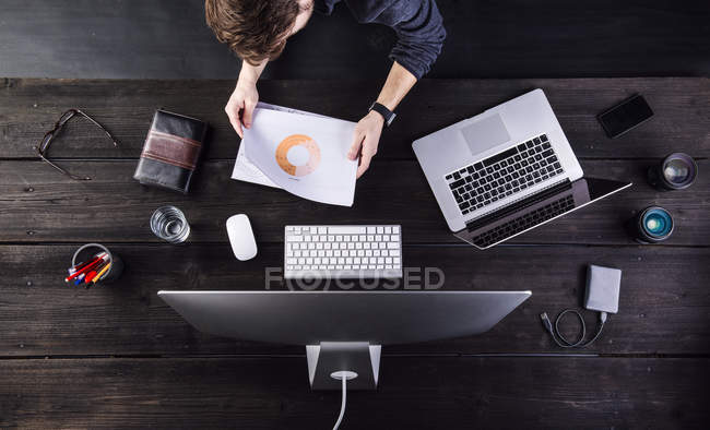 Man working at desk with computer and laptop, looking at charts — Stock Photo