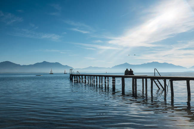 Germany, Lake Chiemsee, Seebruck, two people on wooden jetty — Stock Photo