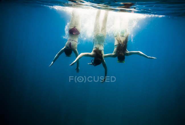 Three girls swimming under water at daytime — Stock Photo