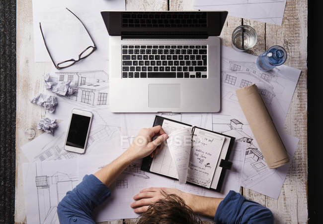 Architect working at desk with laptop, looking at personal organizer — Stock Photo