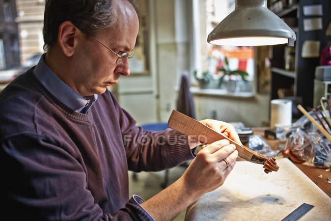 Скрипач осматривает шею инструмента в мастерской — стоковое фото