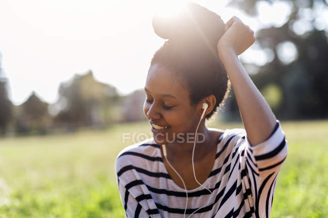 Smiling woman hearing music with earphones — Stock Photo