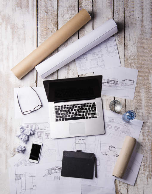 Desk of an architect with laptop and blue prints — Stock Photo