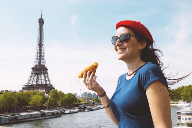 Франция, Париж, женщина с круассаном стоит перед рекой Мбаппе и Эйфелевой башней — стоковое фото