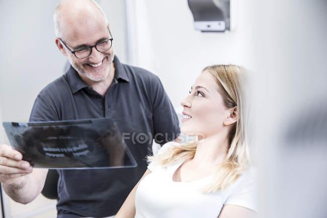 Дантист показывает рентгеновское изображение пациенту — стоковое фото