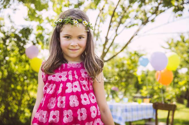Ritratto di ragazza in piedi davanti al suo tavolo di compleanno in giardino — Foto stock