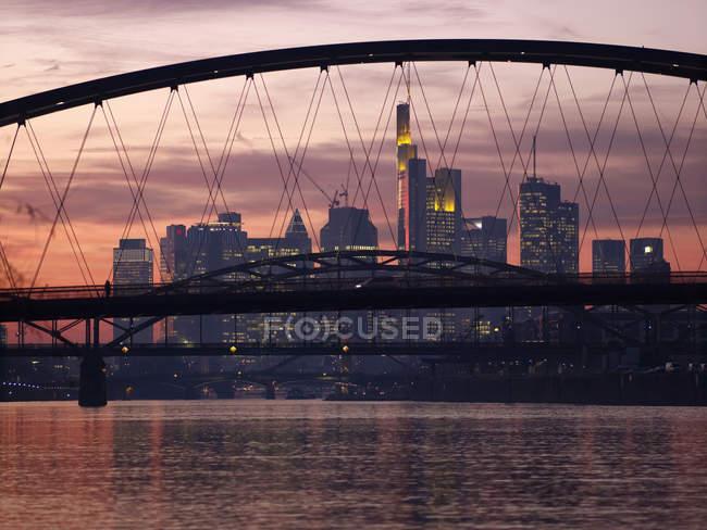 Deutschland, hessen, frankfurt, neue osthafenbrücke mit skyline bei untergang — Stockfoto