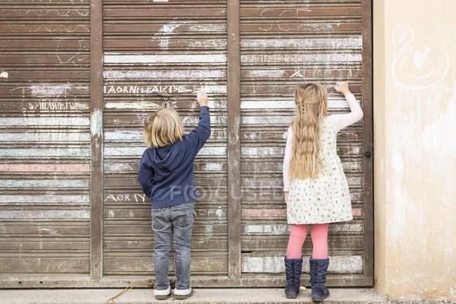 Вид сзади на двух маленьких девочек, рисующих на старой двери гаража — стоковое фото