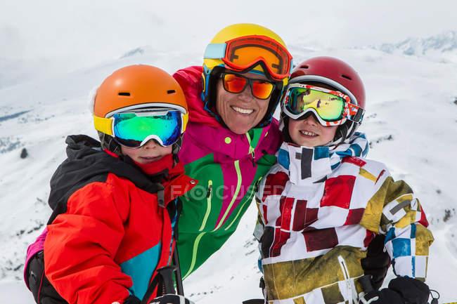 Портрет улыбаясь лыжница и сыновей на горнолыжном курорте — стоковое фото