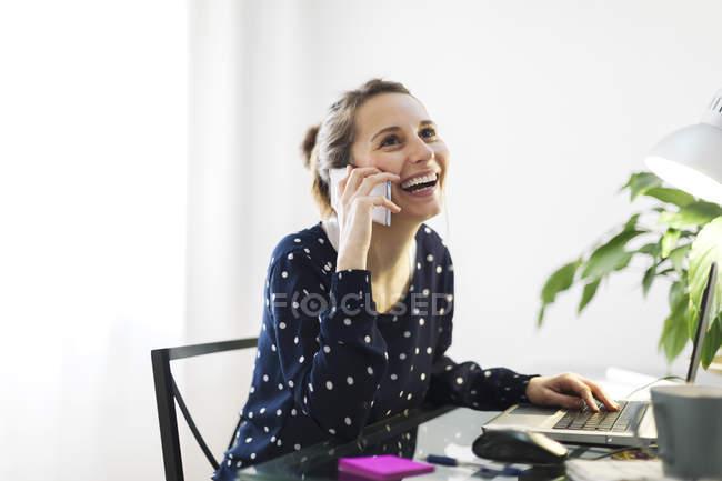 Jeune femme téléphonant avec smartphone à la maison — Photo de stock