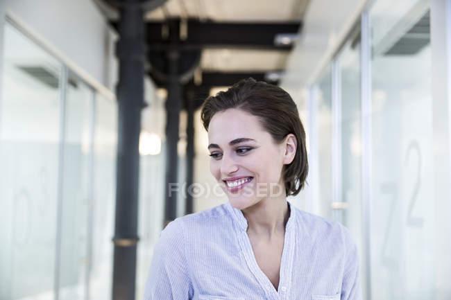 Donna sorridente in un corridoio — Foto stock