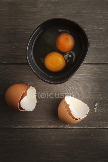 Bowl of two open eggs and eggshell on wooden table — Stock Photo