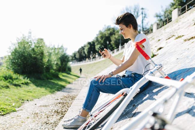 Jovem sorridente com bicicleta e telefone celular sentado na parede inclinada — Fotografia de Stock
