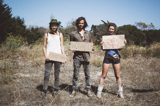 Three hippies holding 'I love you' signs in the nature — Stock Photo