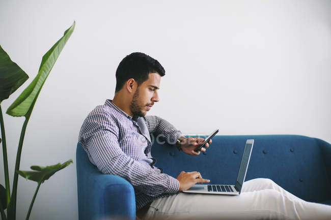Businessman sitting on couch in office using laptop — Stock Photo
