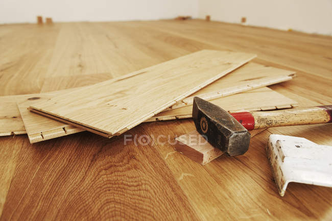 Laying finished parquet flooring and hammer, close-up — Stock Photo