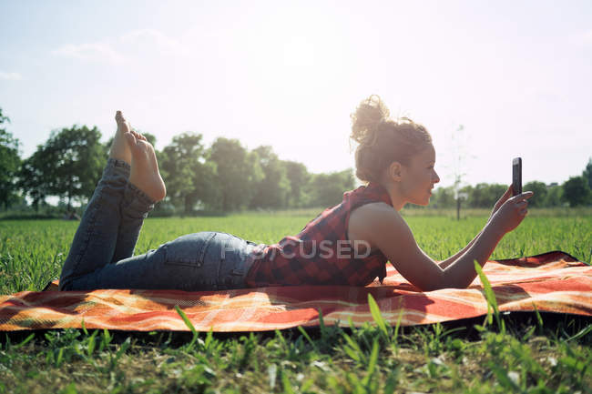 Woman with smartphone lying on blanket on a meadow — Stock Photo