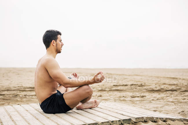 Young man practicing yoga on boardwalk on beach — Stock Photo