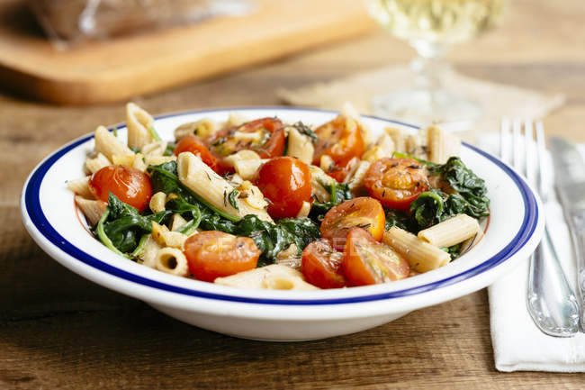 Wholegrain penne pasta with spinach, garlic and tomatoes — Stock Photo