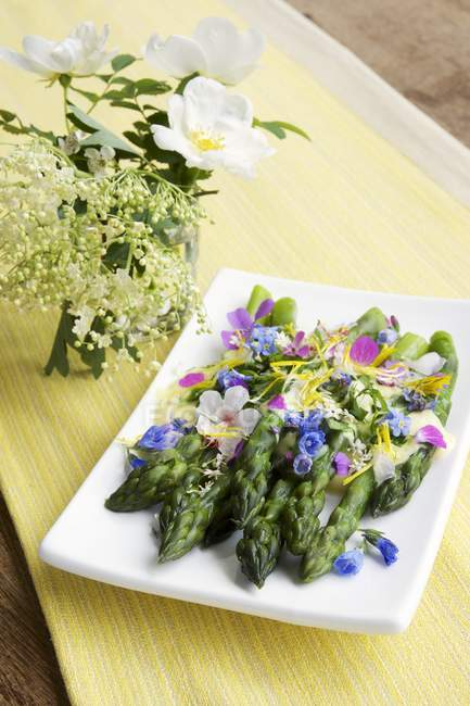 Green asparagus with saffron sauce and edible flowers on plate — Stock Photo