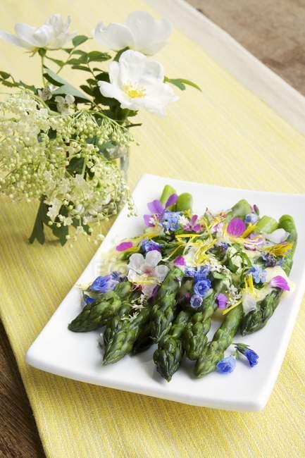 Зеленоголовая спаржа с соусом Шафран и съедобные цветы на плите — стоковое фото