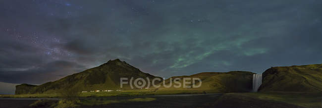 Iceland, Northern lights and milky way at cloudy night over scenic landscape with mountain and waterfall — Stock Photo