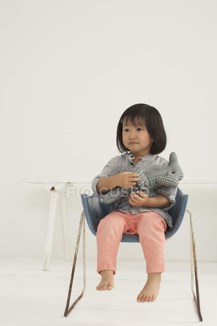 Little Asian Girl With Soft Toy Sitting On A Chair Stock Photo