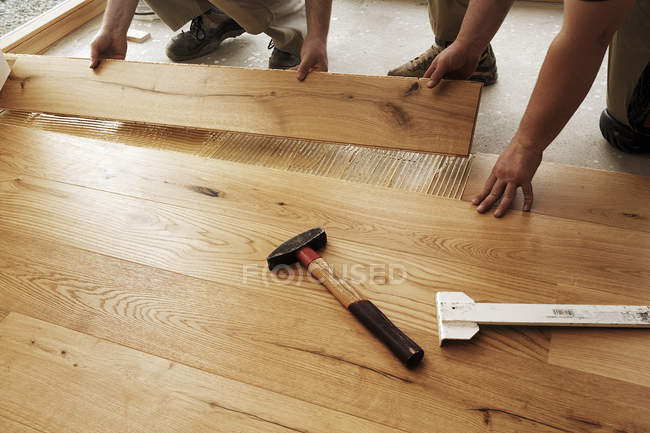 Two men laying finished parquet flooring, close-up — Stock Photo